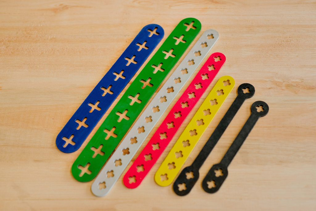 Tiras de borracha coloridas com perfurações em formato de cruz em vários tamanhos sobre uma superfície de madeira.