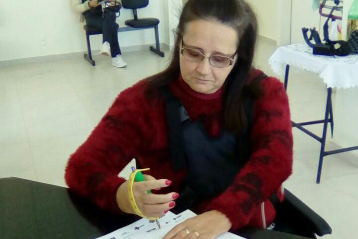 Mulher sentada escreve em um papel sobre a mesa com a ajuda do Engrossador e Fixador em Tira para segurar a caneta com a mão direita.