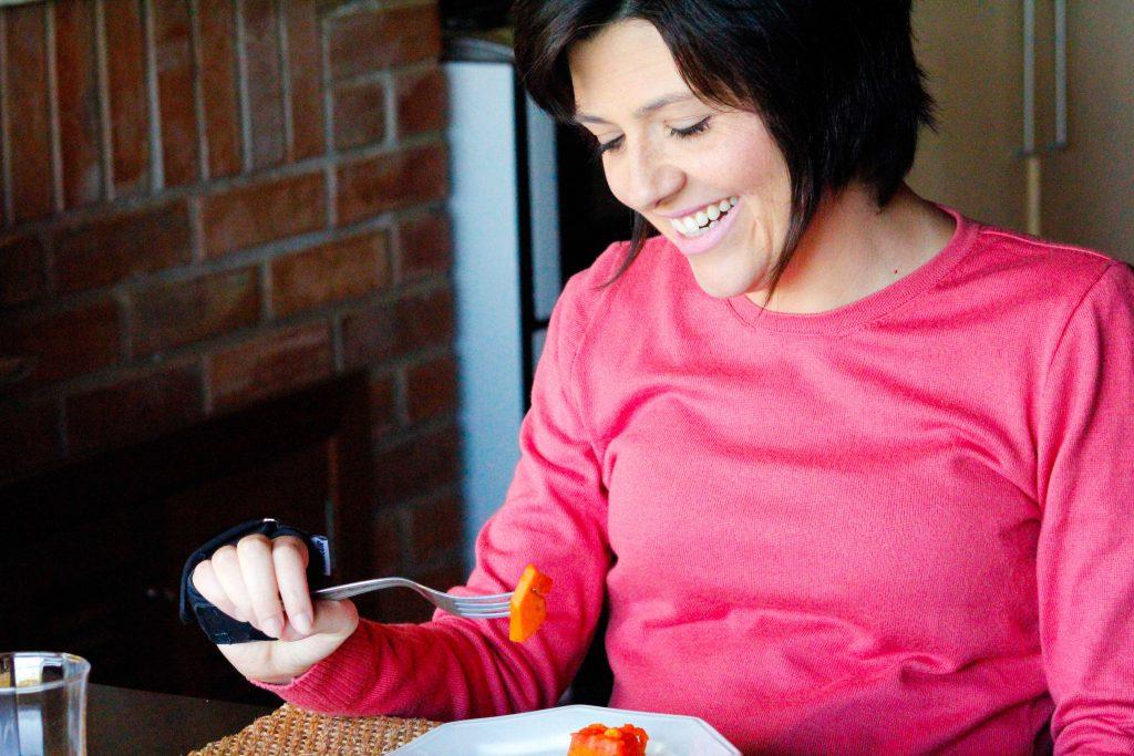 Uma mulher está sentada à mesa e segura um garfo na mão direita com ajuda do Fixador Multiuso, que é uma tira de tecido preto com velcro, no qual é possível prender utensílios.