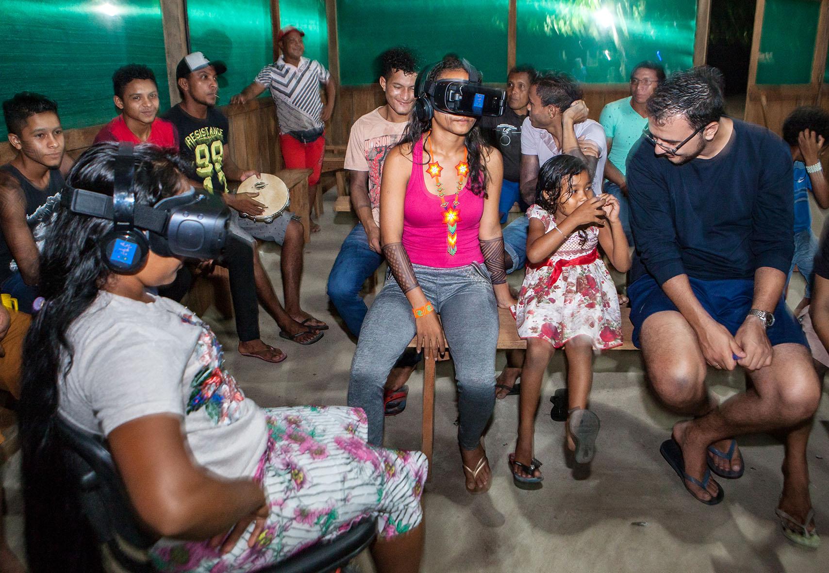 Várias pessoas estão sentadas próximas em bancos de madeira. Duas mulheres do grupo estão usando óculos de realidade virtual.