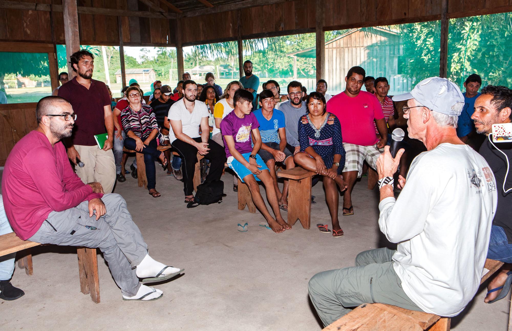 Dois homens sentados em um banco de madeira, um com um microfone nas mãos, estão de frente para um grande grupo de pessoas que os ouvem com atenção.