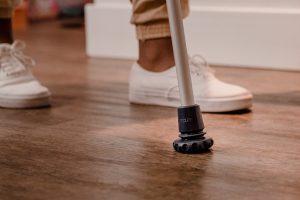 A imagem mostra os pés de uma mulher apoiando a ponteira articulada de uma muleta no chão.
