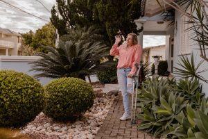 Mulher com uma perna amputada está de pé utilizando muletas na frente de uma casa, abanando para a rua.