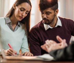 Jeune couple signant une offre d'achat immobilière