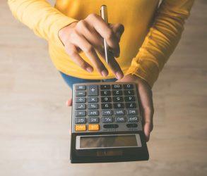 Femme calcule frais immobilier à l'aide d'une calculatrice avec un stylo à la main