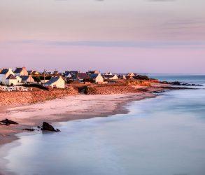 Coucher de soleil donnant une couleur rosée aux bâtiments blancs ainsi qu'au ciel et au sable. Pose longue sur une plage du Finistère (Bretagne- France), non loin de la ville d'Audierne. -