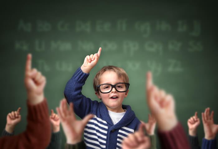 School child with hand raised in the classroom