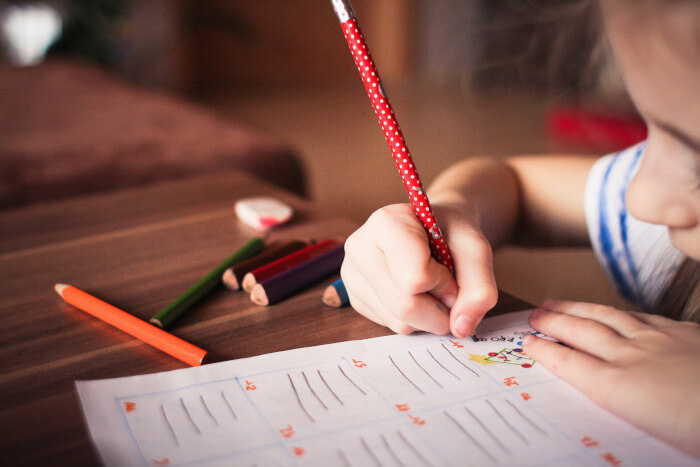 Child working on a piece of paper with multiple crayons