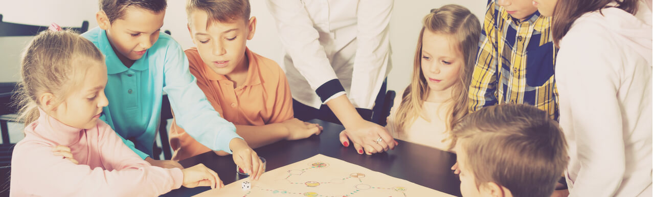 Teacher and happy children with students sitting at table with board game and dice in school