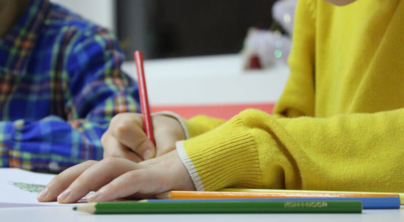 Child writing in his notebook in class