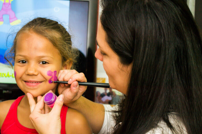 teacher painting a flower on the face of a girl