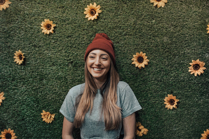 Girl wearing a winter hat smilling with a fake grass wall behind
