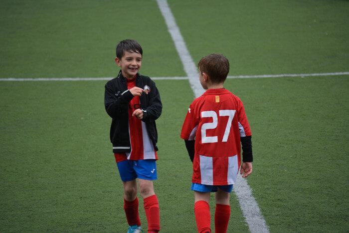 2 kids in soccer uniforms in the rain