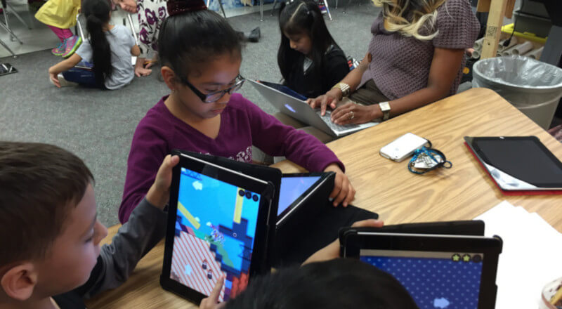 students in their 1st grade classroom using tablets for their class