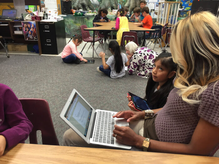 Teacher sitting with her laptop showing something to a student with a tablet