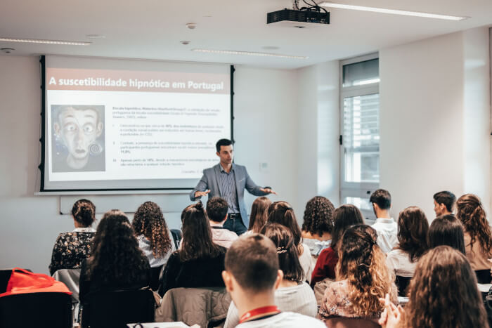 teacher in front of his class showing a presentation in portuguese