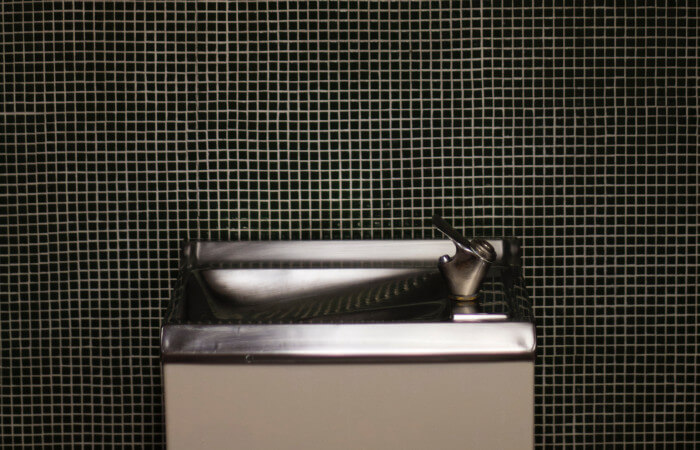 water fountain with a dark ceramic wall behind