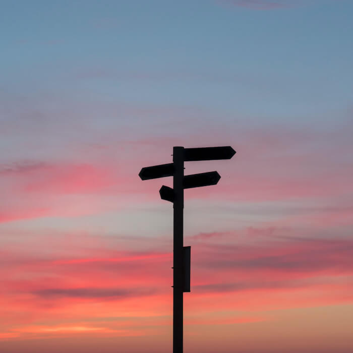 crossroad signs with a sunset in the back
