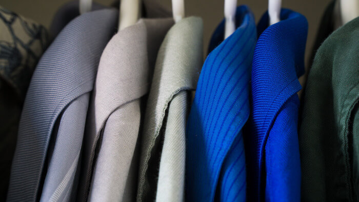 open closet with 3 grey vests and 2 blue