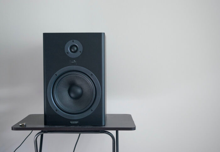 A speaker on a table with a white wall behind