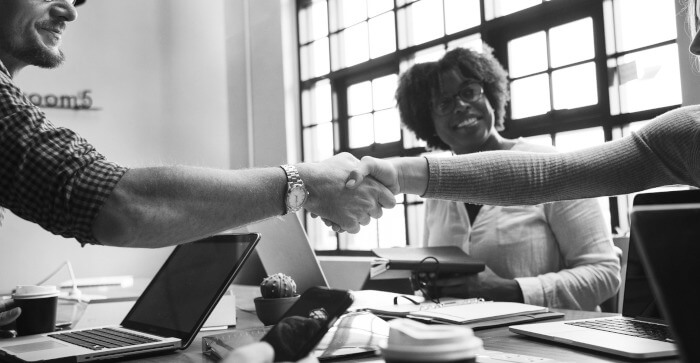 grayscale of people shaking hands in a meeting
