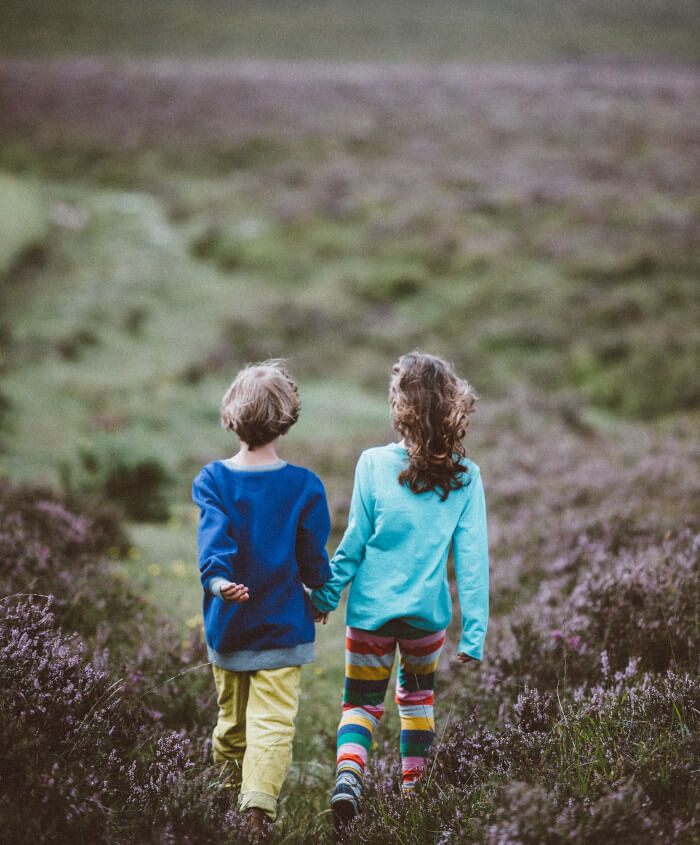 two kids hand in hand walking in a field