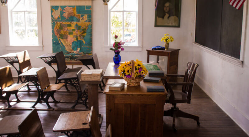 empty classroom with flowers on the teacher desk and a us map between 2 windows