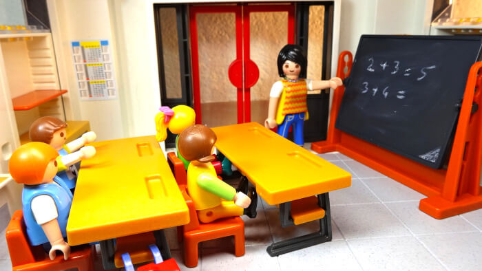 Playmobil classroom with the teacher pointing a board with some math on it