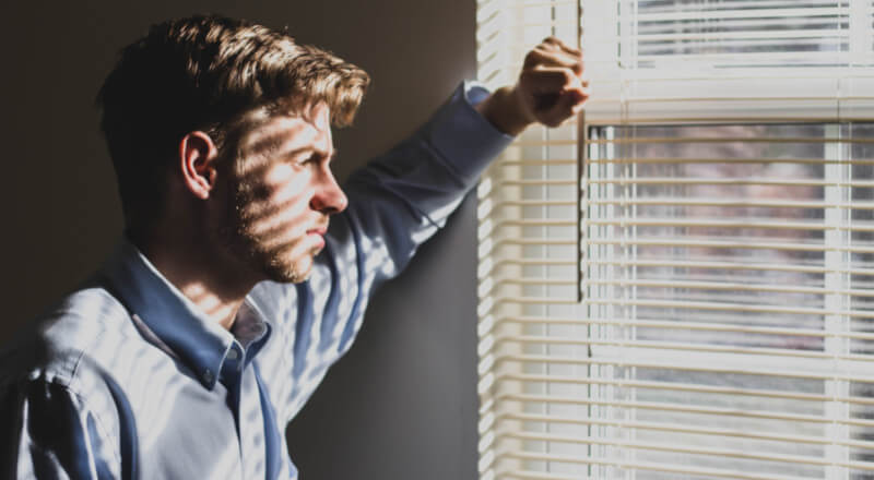 man looking through a window blind with a serious look