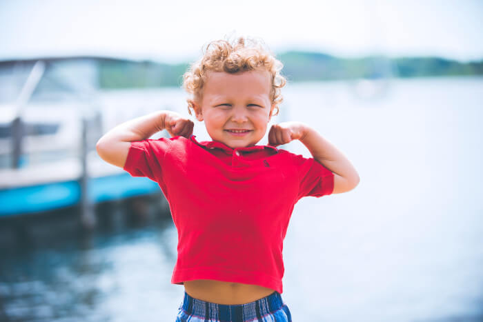 Young boy with blond curly hair flexing his arms