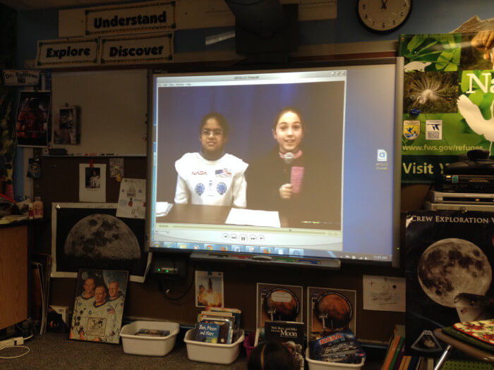 A video on a projector of 2 students disguised as astronaut and reporter