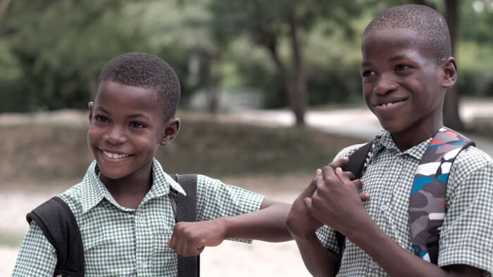 two boys smiling with their backpacks
