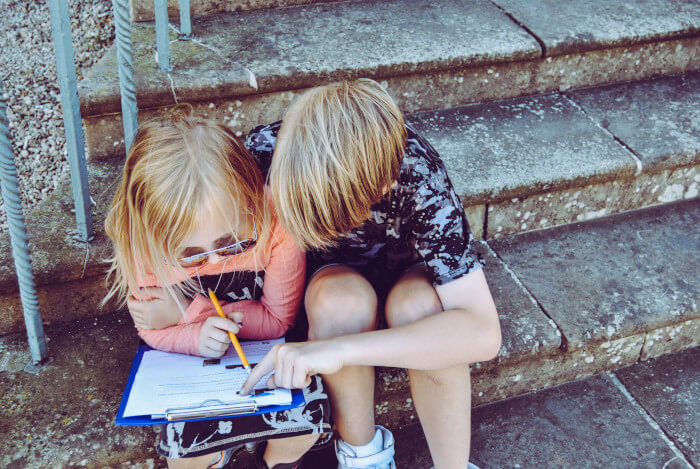 boy helping his sister with her homeworks