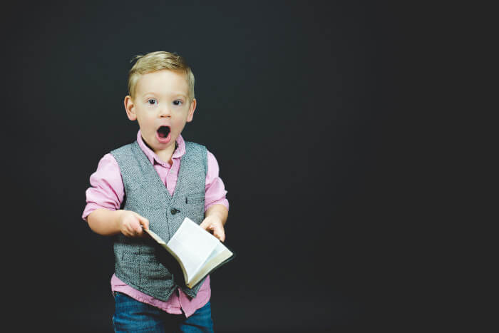 child with a book in his hands looking surprised