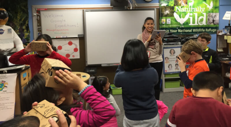 teacher in front of her class with an ipad with her students using google cardboard VRs