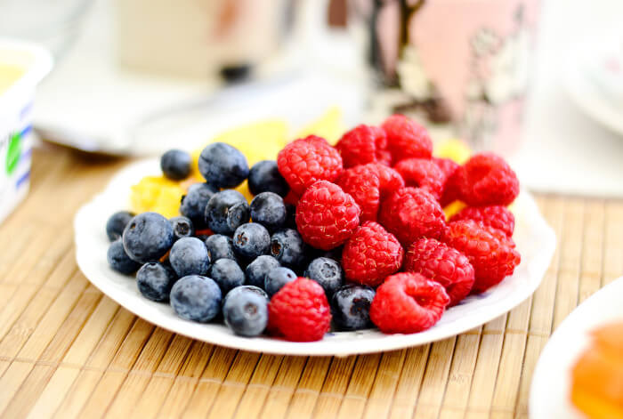 plate of fruits with blueberries and raspberries