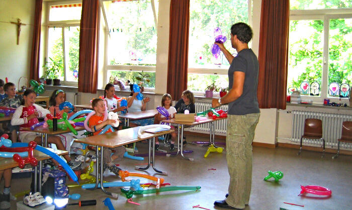 teacher showing a balloon in front of a messy classroom with balloons everywhere