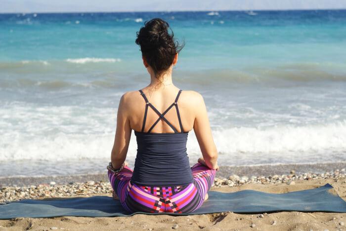 woman meditating at the beach on a yoga matress
