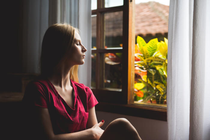 woman meditating with her eyes closed her head turned in the direction of the window