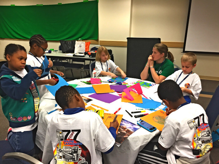 Group of student seated around a table working on a project with the teacher seating with them and helping