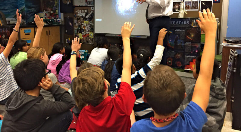Teacher showing a galaxy on a projector with the students rasing hands