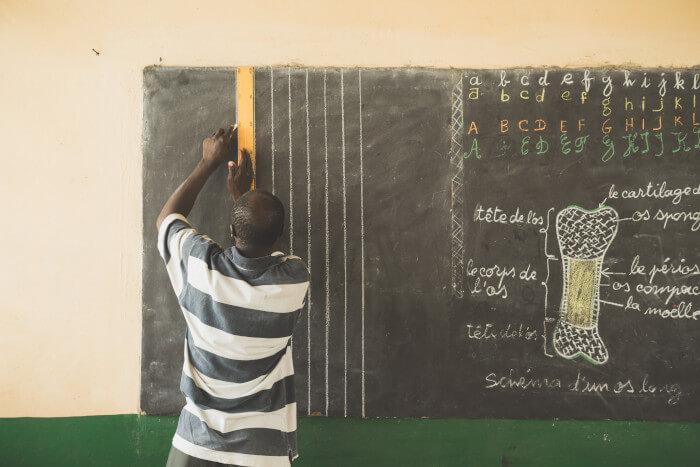 teacher writing on a black board