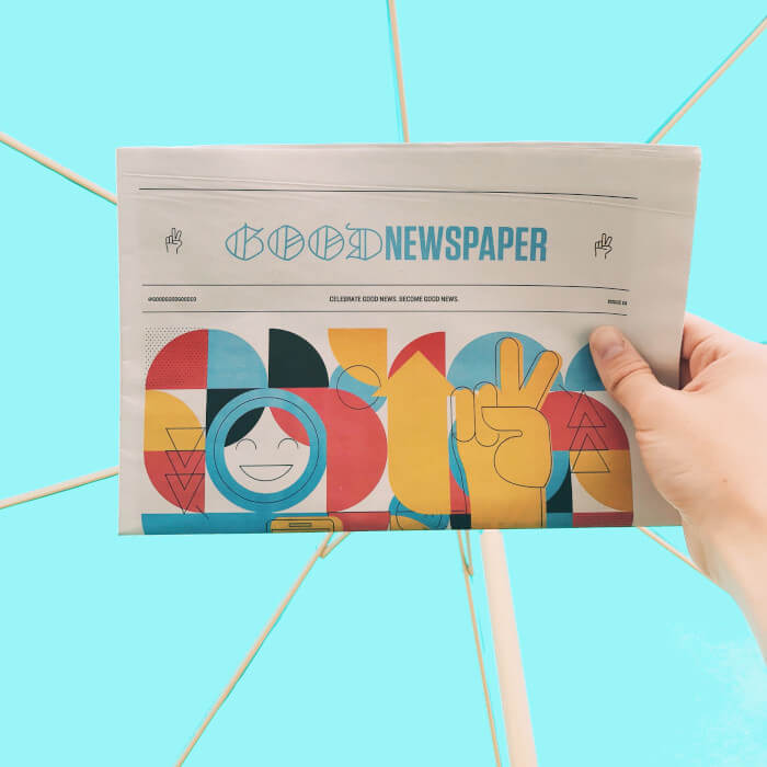 a hand holding a newspaper on a blue background