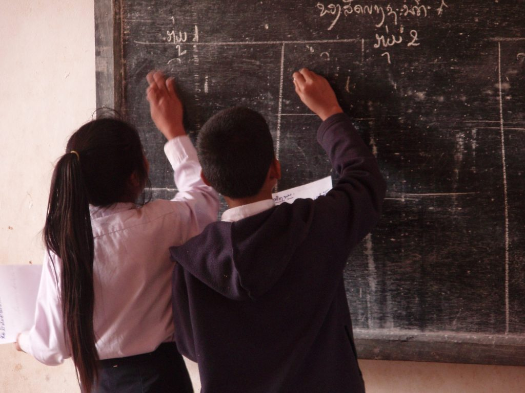 students writing on blackboard