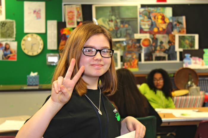 girl student smiling doing a peace sign looking back a the camera