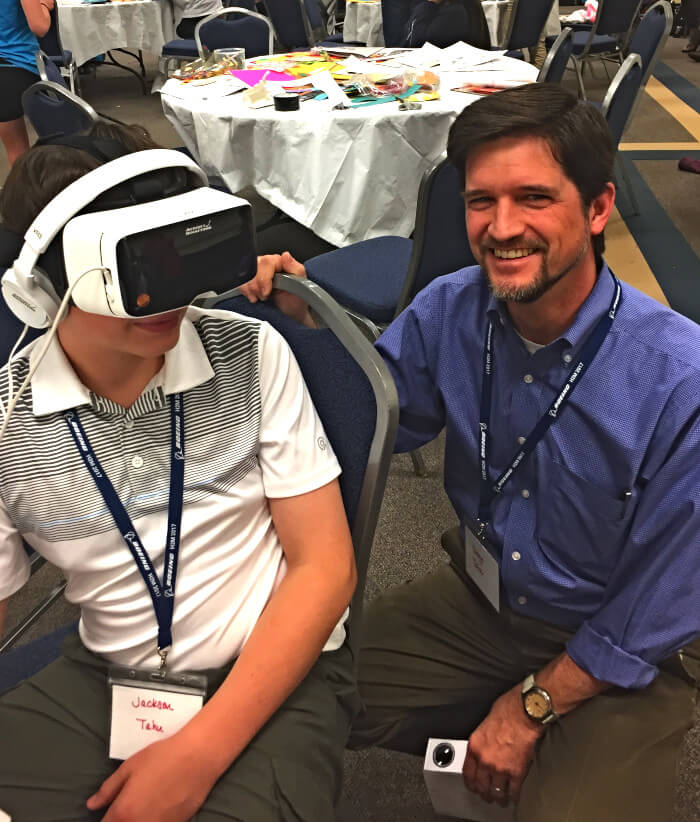 student using a vr headset with his teacher at his side