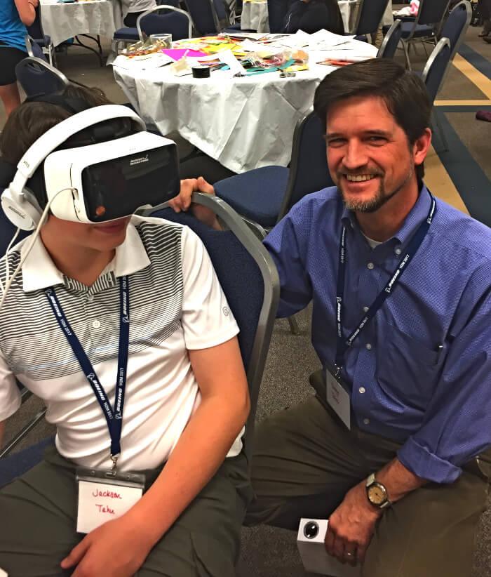 estudiante usando un auricular vr con su maestro a su lado
