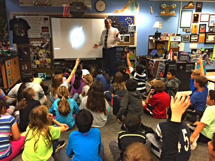Profesor mostrando una galaxia en un proyector con un par de estudiantes rasing hands
