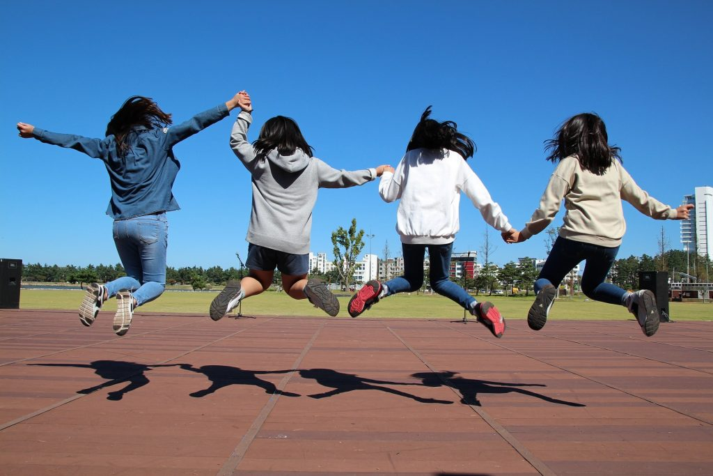 Middle school students jumping.