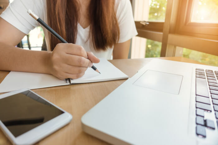 person with long hair writing on a paper with a laptop in front of her